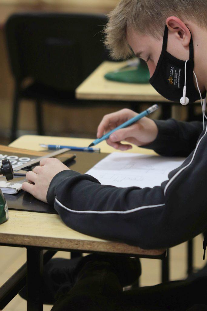 Chłopak z ołówkiem w ręce patrzący na kartkę papieru